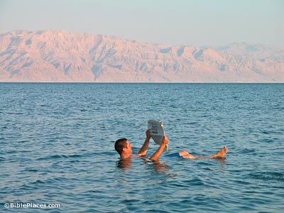 Man floating in Dead Sea reading newspaper