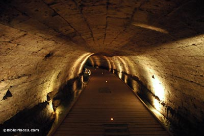 A dimly lit tunnel with a wide wooden walkway.