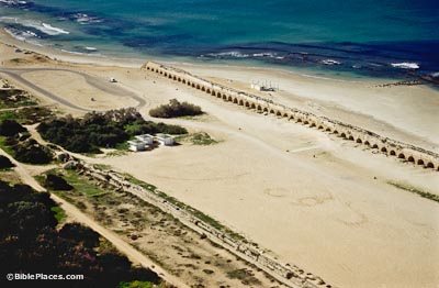View from airplane of a beach with a long aqueduct, raised by arches, ending at the sea, the aqueduct has some plants growing on the top of it