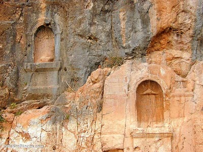 Two arch-shaped recesses carved into a rock face of a mixed grey and orange color