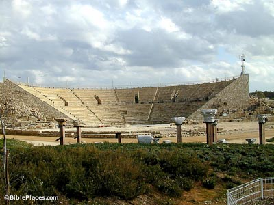 A large semicircular stone structure with rows of seats all around facing a low stone platform on the ground, some piece of pillars are stood up on wooden structures in the foreground
