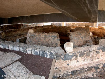Two low basalt walls forming concentric octagons, with a modern ceiling looming low over the structure