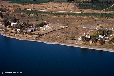View from airplane of ruins and modern buildings on the shore of the Sea of Galilee, with a group of trees further inland