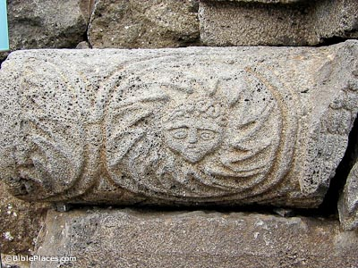 A porous grey stone cylinder on its side with a carved image of a face surrounded by a spiral of rays (like sun rays)