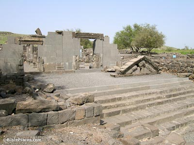 A wide basalt stairway leading up to basalt ruins and the partially reconstructed walls of a stone structure