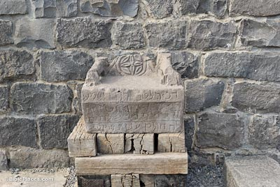 A square rock base of a seat on a wooden platform, the front of the seat has an Aramaic inscription and the back of the seat a carved image similar to a compass rose