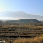 A dirt field with bare trees behind it overlooked by low hills and a mountain