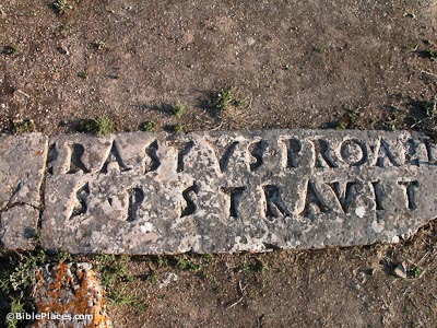 paving stone in ground with deeply etched letters reading Erastus