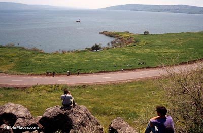 View from a cliff where people sit looking down at a road bisecting a green slope leading down to a cove