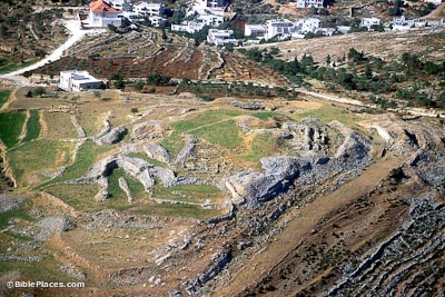 View from airplane of an open, elevated area with some patches of grass, dirt and stony sections, as well as some visible excavations