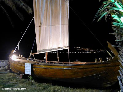 A picture taken at night of a long, low wooden boat with a rectangular cloth sail and rigging; city lights are visible in the far distance