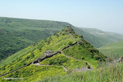 A green peak with stone paths and structures leading up the peak, rolling hills in the background