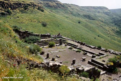 A rectangular stone foundation nestled on a grassy slope, parts of steps and columns jut from the structure