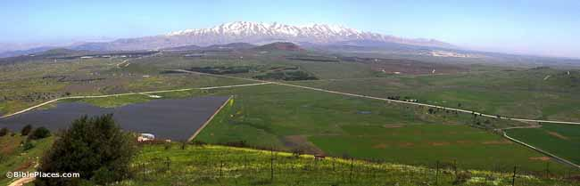 A wide view overlooking a plain with crossing roads and fields with a snowy mountain range looming in the distance