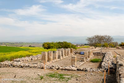 Roughly hewn pillars forming a flanked path through the middle of a structure enclosed with a rectangle of heaped stones, surrounded by dirt and grass overlooked by a blue sky streaked with clouds