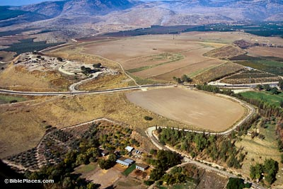 View from airplane of a wide brown valley with roads dividing fields, there are some modern buildings in the foreground