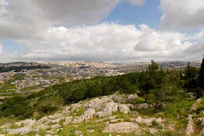 View from a green, rocky slope toward a distant ridge covered in buildings, with a blue sky full of fluffy clouds