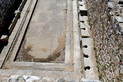 A rectangular stone area, lined on the two long sides with benches that have openings at regular intervals