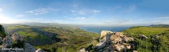 A panoramic view from a tall rocky cliff overlooking green hills on either side of a valley; the Sea of Galilee is visible, as well as some buildings and roads on the plain
