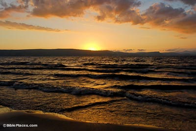 View from a beach at sunset, with low waves reflecting the light from an almost vanished sun in a partly cloudy sky