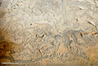 A partially-eroded mosaic depicting the Nile River, predators (such as lions), prey (such as deer), flowering plants, horsemen, and a tower-shaped structure