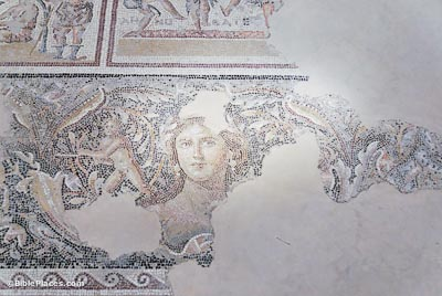 A partially-preserved mosaic on white stone depicting a woman's face surrounded by colorful designs and a winged figure