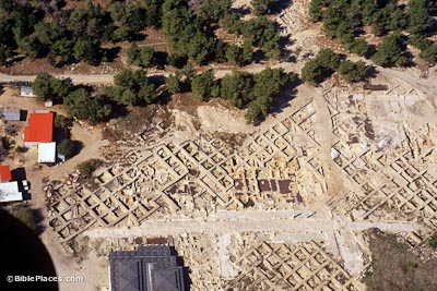 View from airplane of a dirt area with archaeological excavations forming a grid pattern