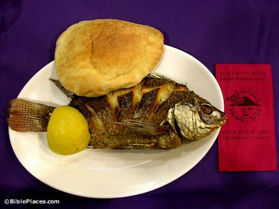 A whole cooked tilapia, a wedge of lemon, and a piece of pita bread on a round white plate, with a purple tablecloth and red napkin