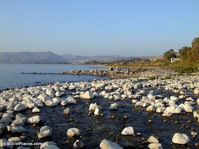 Shallow water on the Sea of Galilee's shore with many scattered rocks and a stone breakwater, vegetation is visible on the near shore and hills are visible through the haze on the opposite shore