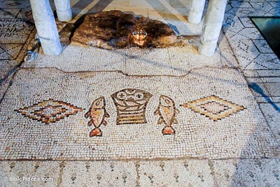 A mosaic of a basket with a fish and a horizontal diamond design on each side, with four slender marble columns standing in a rectangle nearby