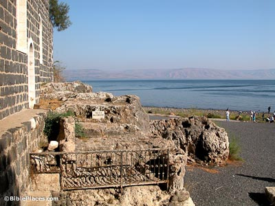 A low rocky outcropping with the wall of a building on the left and a gravel-covered area on the right leading to the Sea of Galilee, on the rocks there is a small fence and a sign that says