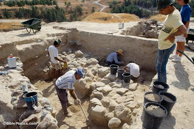 A group of several men working to excavate a rectangular area containing a stone wall