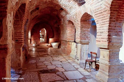 A vaulted brick hallway with arched entryways on either side and stone pavement, a wooden chair is sitting in an archway on the right