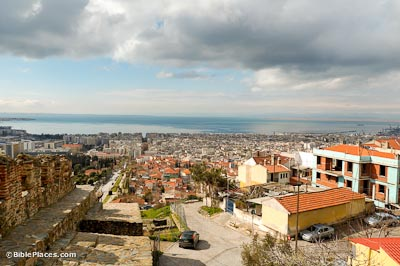 View overlooking a dense city with many orange roofs, in the left corner there are stone and brick ruins, in the distance is the sea with blue sky with some clouds