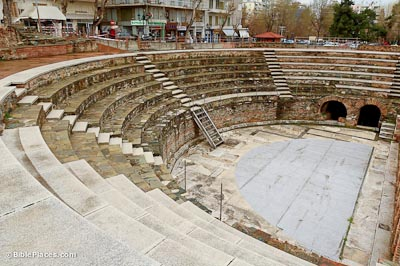 A semi-circular structure with tiered stone bench seating that looks over an empty stage area